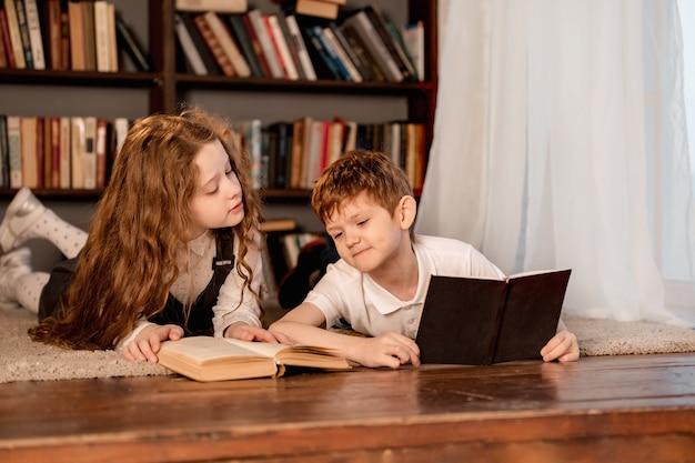 Kleines mädchen und junge, die das buch lesen.