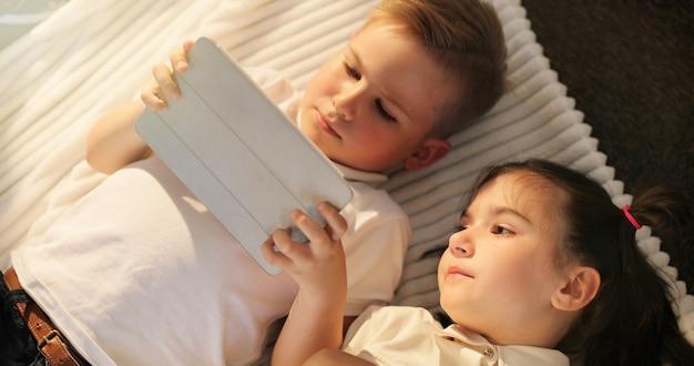 Kleines mädchen und junge, die digitale tabletten verwendet