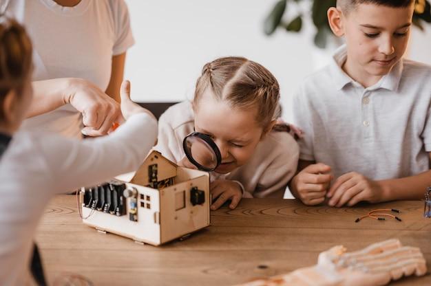 Kleines mädchen und junge lernen über elektrische geräte im unterricht