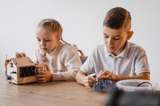 Kleines mädchen und junge lernen über elektrische geräte
