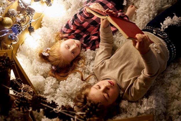 Kleines mädchen und junge lesen ein buch in einem dekorierten raum für weihnachten.