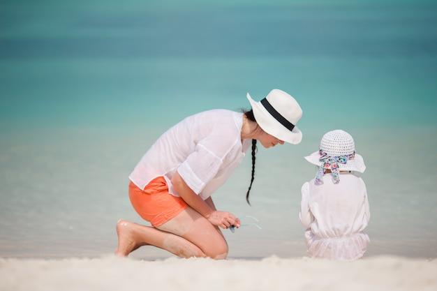 Kleines mädchen und junge mutter während der strandferien