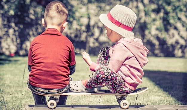 Kleines mädchen und junge spielen auf skateboard, gegen im grünen garten, konzept der kindheitsfreundschaft