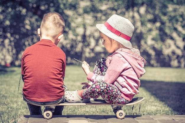 Kleines mädchen und junge spielen auf skateboard, konzept der kindheitsfreundschaft