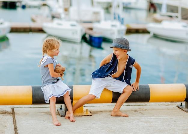 Kleines mädchen und junge spielen mit kleinem rotem hund am seehafen