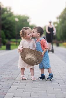 Kleines mädchen und junge umarmen und küssen sie stehen in der mitte der grünen gasse und halten einen strohhut