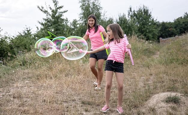 Kleines mädchen und mama spielen mit großen seifenblasen in der natur.