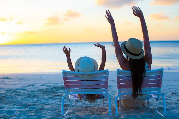 Kleines mädchen und mutter, die auf strandstühlen bei sonnenuntergang sitzt