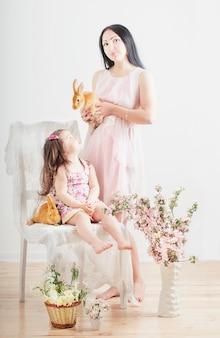 Kleines mädchen und mutter mit kaninchen drinnen