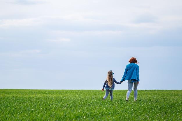 Kleines mädchen und mutterfrau laufen und springen, grünes gras auf dem feld, sonniges frühlingswetter, lächeln und freude des kindes, blauer himmel mit wolken