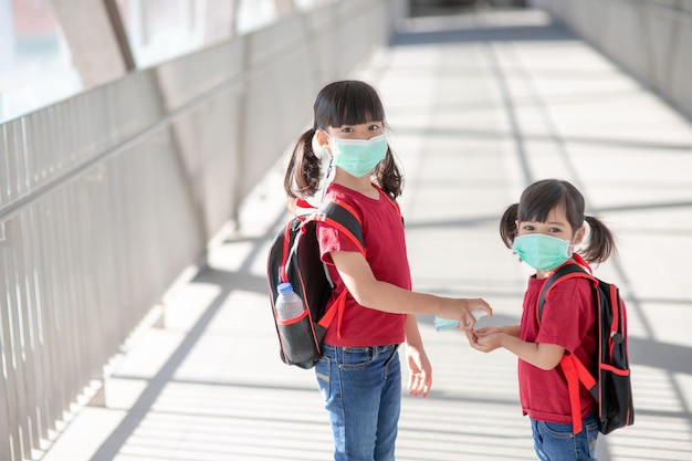 Kleines mädchen und schwester mit gesichtsmaske, die während des ausbruchs des coronavirus zur schule gehen. sicherheitsmaske zur krankheitsprävention. mutter und kind in der schule während der covid-19-pandemien.