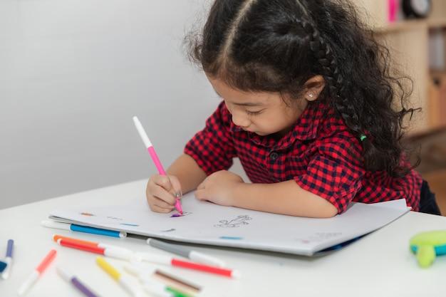 Kleines mädchen und zeichnungsspaß auf dem papierweiß