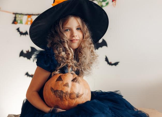 Kleines mädchen verkleidet als hexe mit kürbis. halloween. kürbis für halloween