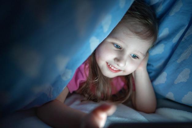 Kleines mädchen versteckt sich unter decke mit smartphone nachts, wenn alle schlafen.