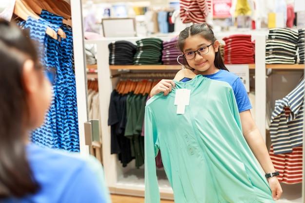 Kleines mädchen versuchte kleidung vor dem spiegel im einkaufszentrum