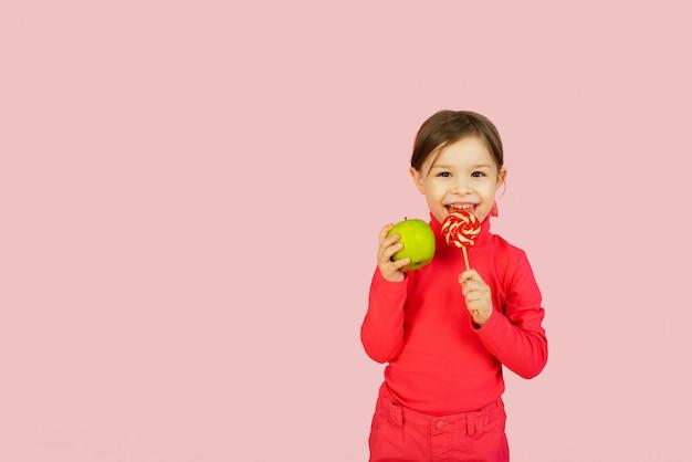 Kleines mädchen wählt zwischen einem lutscher und einem grünen apfel. das konzept der richtigen ernährung. schwierigkeit der wahl