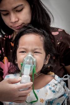 Kleines mädchen weint beim einsteigen in inhalator maske im krankenhaus, dunkler ton