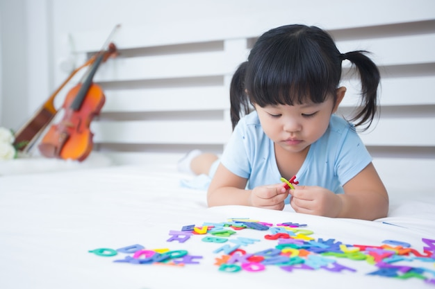 Kleines mädchen, welches das alphabet studiert