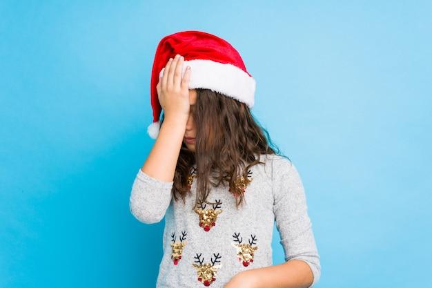 Kleines mädchen, welches den weihnachtstag etwas vergessend feiert, stirn mit palme schlägt und augen schließt.