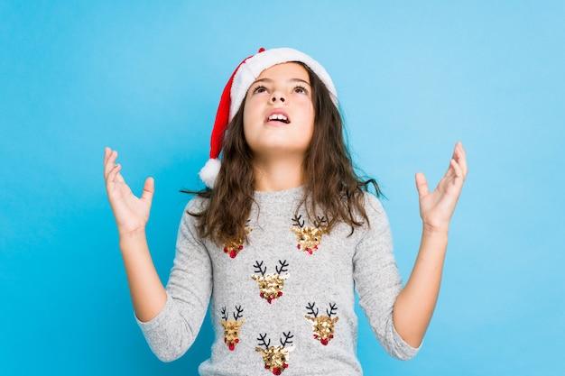Kleines mädchen, welches den weihnachtstag schreit zum himmel feiert und oben schaut, frustriert.