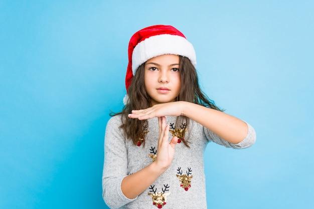 Kleines mädchen, welches den weihnachtstag zeigt eine auszeitgeste feiert.