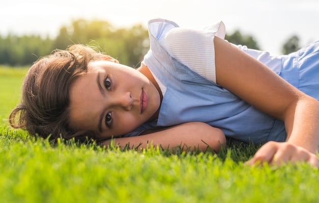 Kleines mädchen, welches die kamera beim bleiben auf gras betrachtet