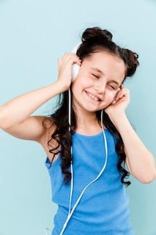 Kleines mädchen, welches die musik an den kopfhörern lebt