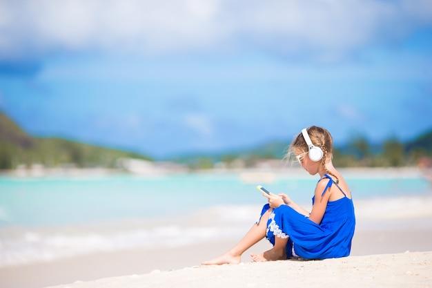 Kleines mädchen, welches die musik durch kopfhörer auf dem strand hört
