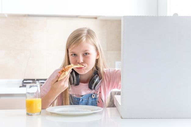 Kleines mädchen, welches die pizza sitzt am tisch isst