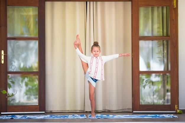 Kleines mädchen, welches die yogaübung im freien auf terrasse tut
