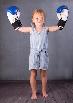Kleines mädchen wie ein champion mit erhobenen händen. kinder- und sportkonzept.