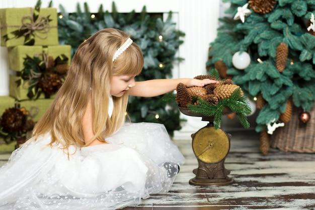 Kleines mädchen wiegt auf der waage tannenzapfen dekorationen für den weihnachtsbaum.