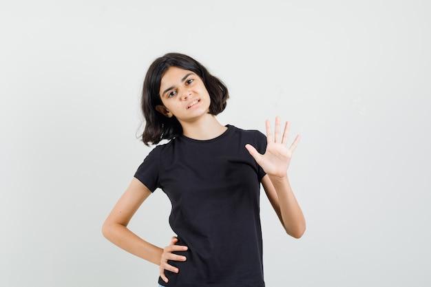 Kleines mädchen winkt hand, um hallo im schwarzen t-shirt, vorderansicht zu sagen.