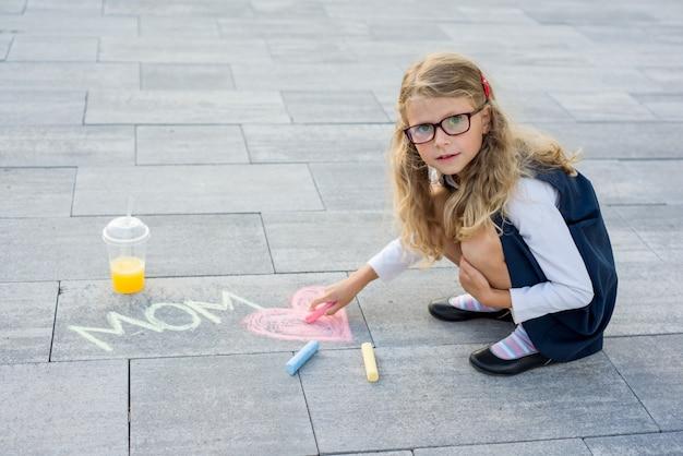 Kleines mädchen zeichnet für ihre mutter eine bildüberraschung von zeichenstiften auf dem asphalt