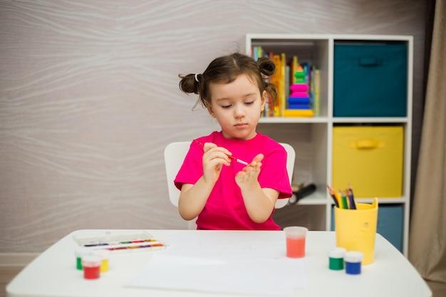 Kleines mädchen zeichnet mit pinseln und farben am tisch