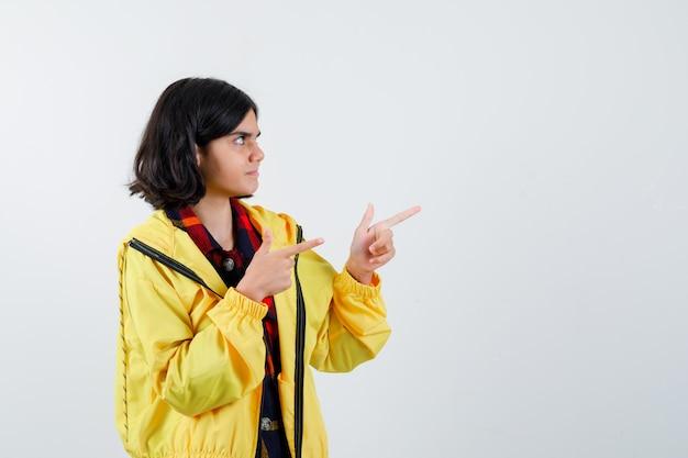 Kleines mädchen zeigt auf die rechte seite in kariertem hemd, jacke und sieht selbstbewusst aus