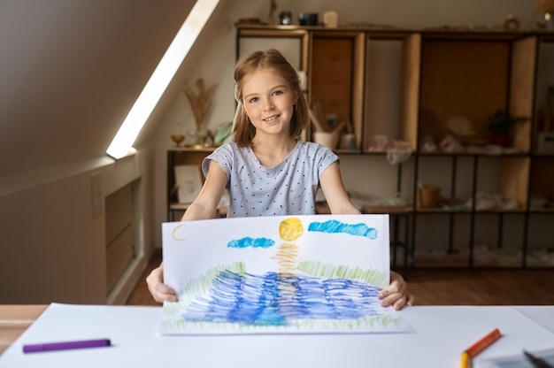 Kleines mädchen zeigt ihre zeichnung, kind in der werkstatt. unterricht an der kunstschule. junger maler, angenehmes hobby, glückliche kindheit. kreative entwicklung