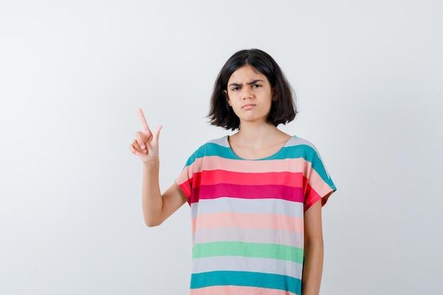 Kleines mädchen zeigt nach oben, verzieht das gesicht in t-shirt, jeans und sieht unzufrieden aus. vorderansicht.