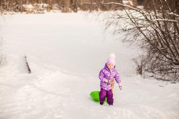 Kleines mädchen zieht einen schlitten am warmen wintertag