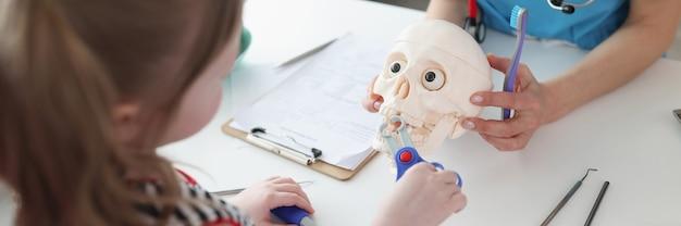 Kleines mädchen zieht zahn mit medizinischen spielzeuginstrumenten auf astronomischem schädel bei zahnarzttermin heraus...