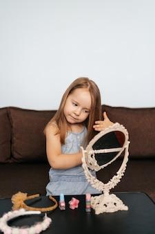 Kleines mädchen zu hause, das auf dem sofa sitzt, ihr haar kämmt oder schönheitsaccessoires verwendet und in den spiegel schaut