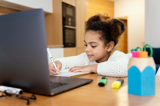 Kleines mädchen zu hause, das während der online-schule mit laptop studiert