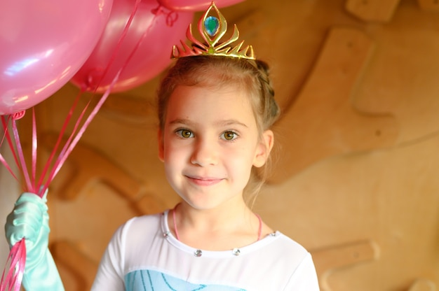 Kleines mädchen zu hause in einem eisprinzessinkostüm mit krone und luftballons feiert ihren geburtstag