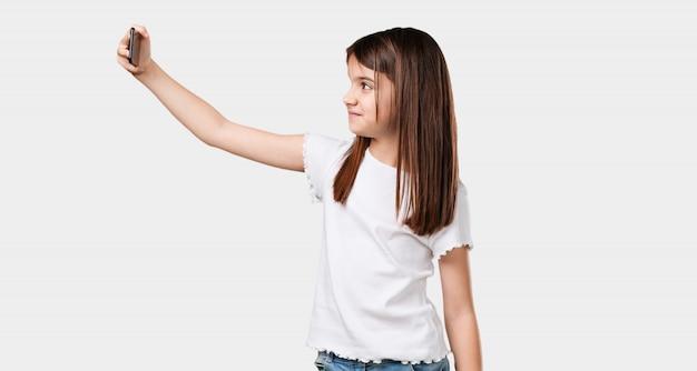Kleines mädchen zuversichtlich und fröhlich, ein selfie nehmend und schaut mit einer lustigen und sorglosen geste auf das handy