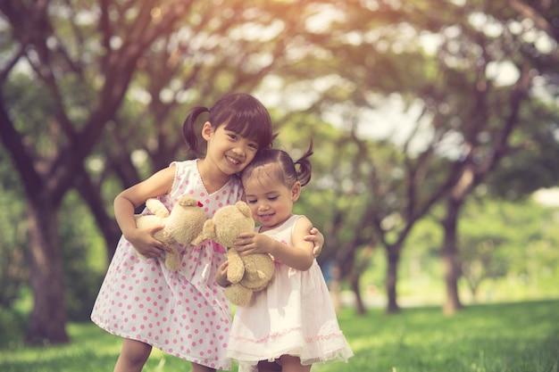 Kleines mädchen zwei, das im wald mit teddybär baer umarmt