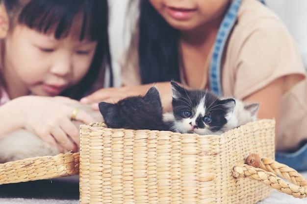 Kleines mädchen zwei, das zu hause mit katze, freundschiffskonzept spielt.
