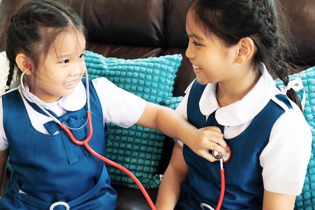 Kleines mädchen zwei lächeln und doktor mit stethoskop spielend. kind und gesundheitskonzept.