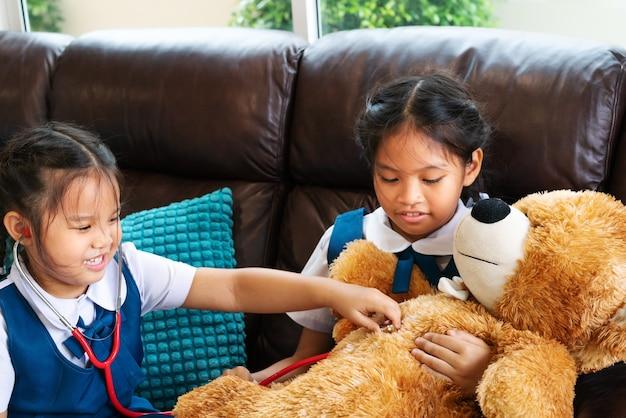 Kleines mädchen zwei lächeln und doktor mit stethoskop spielend.