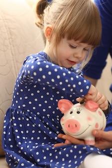 Kleines mädchenarm, der stiftgeldmünzen in glückliches ferkelschlitzporträt mit rosa gesicht setzt. wenn sie effektive einsparungen für die zukunft erzielen möchten, sammeln sie geldgeschenke