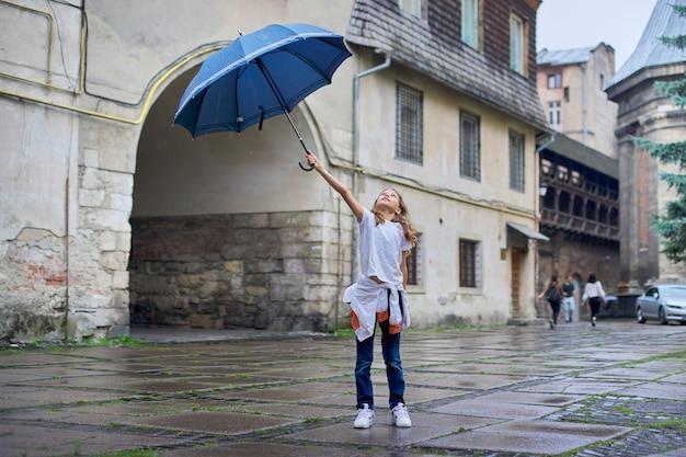 Kleines mädchenkind im regen mit einem regenschirm, touristischer alter stadthintergrund